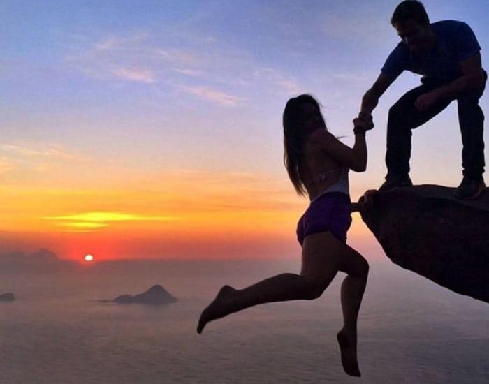 парень держит за руку девушку на скале