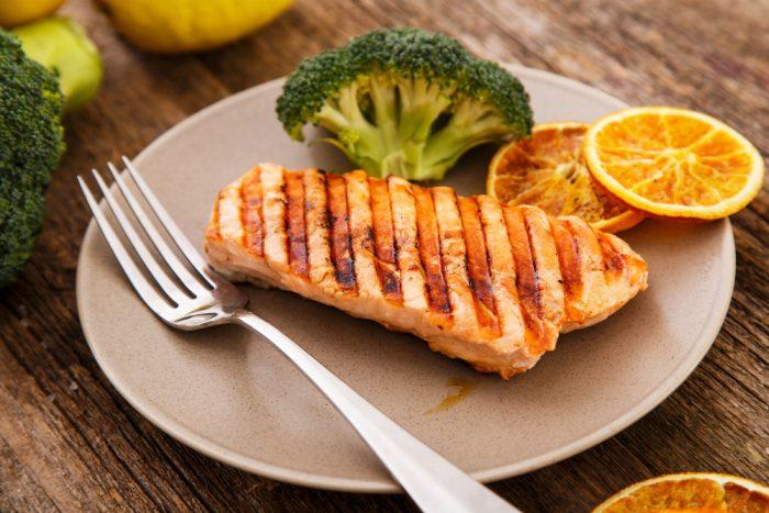 Рыба с гриля на тарелке с капустой и дольками апельсина на тарелке
