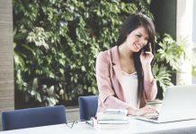 девушка говорит по телефону и работает за ноутбуком
