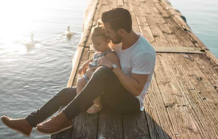отец и дочь сидят у озера