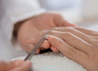 Beautician manicure with nail file in a salon